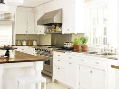 white Kitchen with breadboard and stainless and wood counters. large checkerboard floor in grey and white