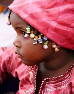 Africa | A little girl watching the goings on at the Voodoo Festival in Ouidah, Benin | ©Corrie de Winter