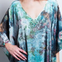 Details of the Mirage maxi caftan dress- 100% silk hand-dyed in an artistic blend of blue, green and plum tones with hand-embellished lace and fire agate beadwork at the neckline. Each piece is sewn, dyed, painted and beaded by hand, with love in NYC.