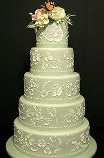 This mint green cake with a light green floral pattern and beading is topped with fresh-looking sugar flowers and a butterfly.