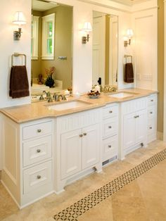 A double vanity adds convenience and elegance to this bathroom with undermount sinks and a plethora of drawer space. Frameless mirrors reflect light and add depth to the space, while an inlaid border adds dimension to the tile floors.