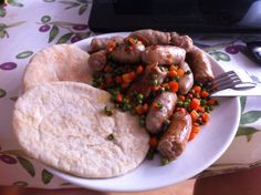 Pork sausages with carrot and peas, pita bread.