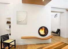 """At first I thought this fireplace was a washing machine, but it's a custom round door for a wood-burning fireplace with a heart wood """"mantel"""" below the fireplace. Source: Houzz.com"""
