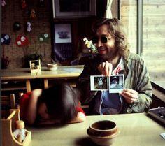John Lennon muestra dos fotos Polaroid, a la dercha se aprecia parcialmente una SX-70