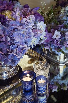 Purple hydrangeas and orchids look opulent in silver vases. || Colin Cowie Weddings