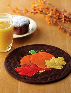 This mini mat features an appliqué pumpkin and leaf design on a brown background. These mini mats can be used as a mug mats, hot pads or trivets.