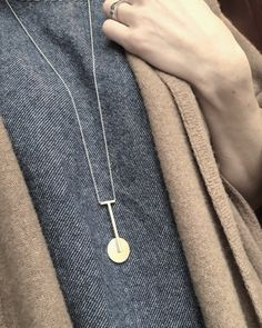 Hand fabricated modernist style pendant in brass on a simple sterling silver chain. Brass develops a lovely patina over time.  Chain Length approx. 30  Pendant size approx. 1.75x.75
