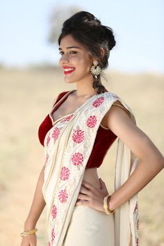 Featuring a cream colored pure Georgette Saree with red Camellia floral embroidered trims along the edges. Saree is pleated at the bottom and decorated with large pearls. Trims are also decorated with pearls and warm gold branches. It comes with an un-stitched red velvet blouse with a pearl border on ETSY.   Please also visit our website at www.eastandgrace.com
