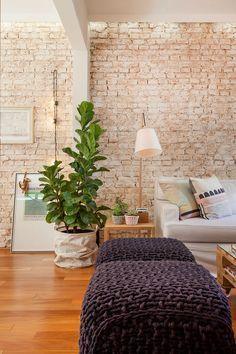 parede tijolinho, pufe trico cinza chumbo, preto, sofa, luminaria, abajur