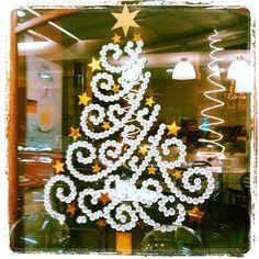 Arbol de navidad (pino de navidad) hecho con tapones blancos sobre el cristal de una tienda