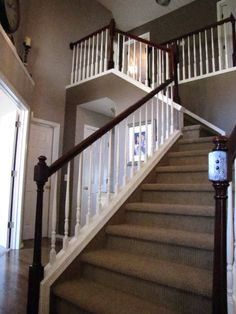 """The """"after"""" picture of the foyer.  The banister and end posts were stripped and stained with a red mahogany and 76 spindles were painted a creamy white.  The walls were finished in a deep chocolate on the back walls and a lighter shade on each additional wall."""