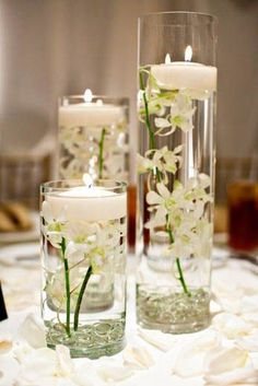 Varying glass cylinders filled with floating candles and submerged flowers