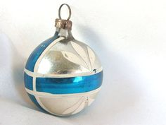 This vintage Christmas ornament is a small, round silver ball with a white framed blue cross around it. There are hand painted white petals.