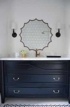 This beautiful black and white bathroom features black and white hex tiled floor as a base for a black washstand with white marble countertop which matches nicely with the gold faucet and brass scalloped mirror flanked by Longacre Sconces.