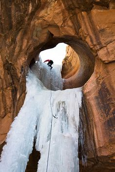Ralph Ferrara climbing an amazing ice route through a sandstone arch in Utah.