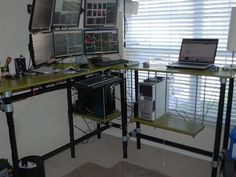 Multi-monitor, multi-terminal standing desk that was constructed with MDF, black fence post and Kee Klamp pipe fittings.