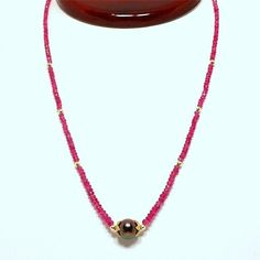 A 16 in. (40.6 cm) designer Pink Sapphire bead necklace, featuring a 9.5mm Tahitian black pearl with 18K & 22K yellow gold.