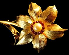It is a gold tone with incredible detail. It has a faux pearl center surrounded by tiny red rhinestones.