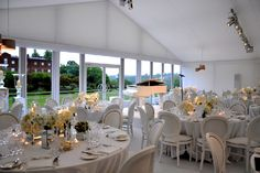 Crisp white decor with clusters of mirrored vases and glass tea light votives for beautiful centrepieces