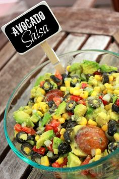 Avocado Salsa 1-2/3 cups Corn 2 cans sliced ripe olives, drained 1 can of Rotel tomatoes, drained 1 medium sweet red pepper, chopped 1 small onion, chopped 5 garlic cloves, minced 1/3 cup olive oil 1/4 cup lemon juice 3 tablespoons apple cider vinegar 1 teaspoon dried oregano 1/2 teaspoon salt 1/2 teaspoon pepper 4 medium ripe avocados, peeled Tortilla chips