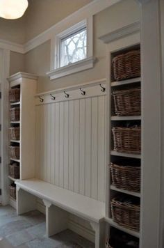 Mudroom with built-in bench seat, wainscoting beadboard wall with hook rail, and neighboring tall cubby shelves with baskets