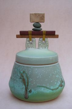 Michael's porcelain covered jar with wood and stone in the handle. Gems at Sea glaze.