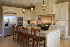 Predominantly white kitchen with stainless steel appliances with white and grey granite counter tops.  4 wood stool chairs line the large island for eat-in area