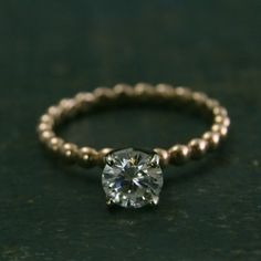 This modern take on a solitaire engagement ring is perfect for any stylish woman. Hand created from our 2.5mm wide beaded rose gold band, I added a premium 14K white gold forged four prong setting. It is securely soldered in place and set with a 6mm Forever Brilliant Moissanite. Your ring will be hand made to size just for you and can be given either a high polished or brushed finish.  For a matching band, please see our other shop: https://www.etsy.com/listing/220072014  ...