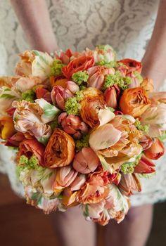 Wedding bouquet in orange and green using tulips, ranunculus, viburnum