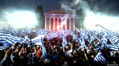Supporters of New Democracy Antonis Samaras wave flags during a pre-election speech in Athens