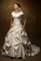 Modest gown with square U neckline and cap sleeves. Pleating over bodice gathered to one side. Pick ups on skirt and train accented with rhinestones.
