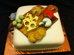 This is a 2 layer vanilla cake with vanilla buttercream frosting and filling. The cake is covered with white fondant and decorated with fondant and gumpaste cheeses. The board is made of gumpaste and stained to look like wood. Peering around the side is a stealthy little mouse looking for a bite of cheese!