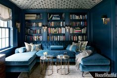 """A Gorgeous, """"Saturated Library : Woodwork is painted a deep, saturated color, Farrow & Ball's Hague Blue, and the ceiling is tented with a Michael S. Smith Indian block fabric, Jasper. Upholstered in a blue Schumacher silk velvet very close to the color of the walls, the tufted U-shaped sofa . . """""""