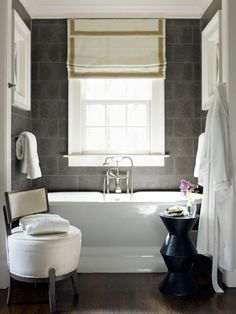 Dixon set up a crisp contrast in the master bath: a white Sunrise Specialty pedestal tub against dark limestone tiles running all the way up the wall. Rivers injected whimsy with a deep-seated slipper chair from Acquisitions.