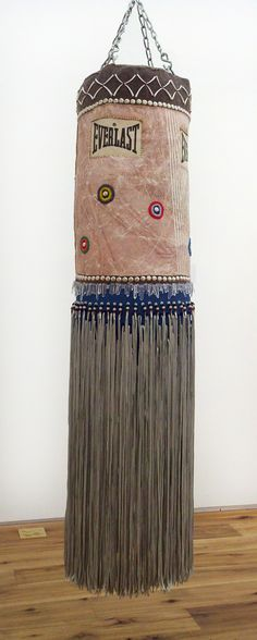 Jeffrey Gibson Everlast (The Quiet One), 2012 -- Found punching bag, wool, repurposed painting, glass beads, dentalium, steel, quartz crystals, artificial sinew, tin cones, nylon shawl fringe