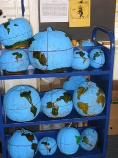 Teaching geography? Make Pumpkin Globes! - Tape down the continents and paint the pumpkin blue. The next day, remove the continents and color them in green with marker. Put two rubber bands around the pumpkin to represent the equator and voila, Pumpkin Globe!