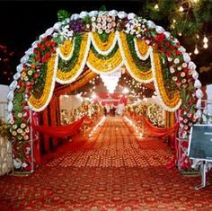 The entrance to the wedding reception venue should provide the much expected prelude to exactly what the guests should expect inside that is it should be as beautiful and captivating as the rest of the venue. Wedding Gate, Wedding Reception Entrance, Wedding Hall Decorations, Marriage Decoration, Wedding Mandap, Flower Decorations, Wedding Dresses, Gate Decoration, Entrance Decor