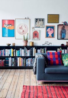Colorfull living room a beautiful wall art, bookshelves and hardwood floors.