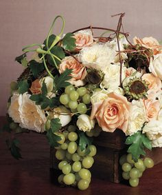 Perfect vineyard inspired centerpiece of garden roses, grape clusters, twigs and vines in a wooden box.