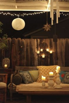 Beautiful and cozy seating area outside, lid up by candles and fairy lights.