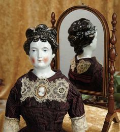 """21""""-German Porcelain Lady Doll with Most Unusual Expressive Features~~~wearing a striped magenta/black silk dress with lace trim, antique cameo brooch, and undergarments. Comments: Germany, circa 1875, A.W. Fr. Kister, an identical model in bisque with blonde hair is shown in Identifying German Parian Dolls by Krombholz. Value Points: rare model with highly characterized features, rare coiffure in usual darkest brown/black shading."""