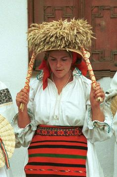 Romanian costume Coşbuc - Bistriţa-Năsăud Wide brimmed straw hat (palarie de paie) worn over a floral printed headscarf. A cununa made of straw is rested on top of the hat. Photo taken at Coşbuc, Bistriţa-Năsăud in July 1991
