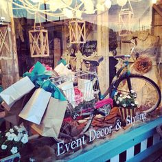 Summer window display.  Yarn wrapped vintage bicycle, lanterns, doily garland, string lights.  Our take on a Shopping Theme.  Post July 4th but not close enough for back to school theme. Find us on Facebook, Resurrected Designs.