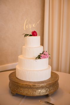 Simple white cake accented with fresh flowers of ranunculus, ruscus, and peonies
