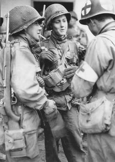 A Medic stops for a chat with some fellow soldiers of the 83d Infantry Division. Werdau, Germany. April 1945.