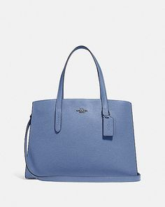 A study in everyday style, the Charlie Carryall is spacious in design and lightweight in feel. The pebble leather silhouette features an organized, thoughtful interior that's perfect from day to night. It fits a 13 Blue Handbags, Kate Spade Handbags, Coach Handbags, Coach Bags, Coach Leather Cleaner, Fashion Handbags, Designer Handbags, Designer Totes, Pebbled Leather