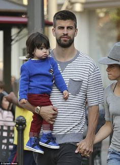 Out and about: The 37-year-old singer held hands with Gerard, whom carried Milan, as the t...