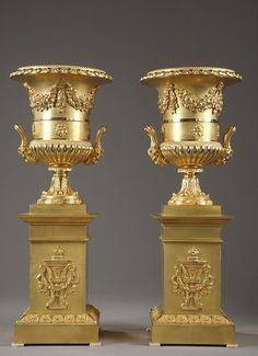 An important pair of Charles X gilt bronze Medici vases decorated with garlands of fruits and flowers in the upper part and godrons on the base, resting on a piedouche...