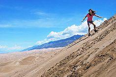 Sandboarding and Sand Sledding at Great Sand Dunes - Girl Sandboarding on High Dune Summit