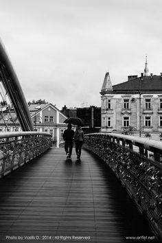 """Together under the rain"" (2014) by Vasilis D.  Kraków, Poland Kładka o. Laetusa Bernatka  URL: www.artfot.net Follow me on twitter: www.twitter.com/vasilisbiz  #afternoon #streetphotography #landmark #bridge #river #Krakow #Poland #blackandwhitephotography #Kladka #Kładka"